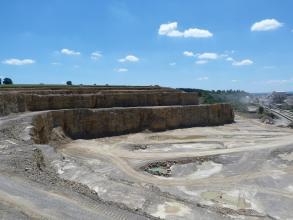 Übersicht über einen Steinbruch, der sich zur rechten Bildhälfte hin öffnet. Es wird auf mehreren Sohlen abgebaut.