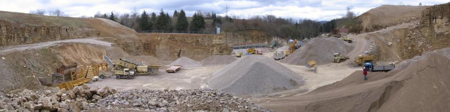 Blick von erhöhtem Standpunkt in einen großen Steinbruch. Es sind Baustellen-Fahrzeuge erkennbar. Das anstehende Gestein ist hellbeige.
