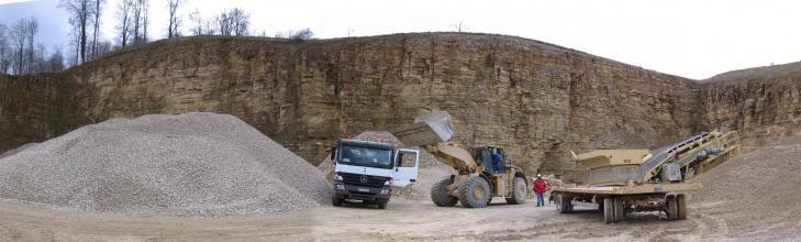 Blick auf eine Abbauwand eines Steinbruchs. Vor der Wand wird gerade Material auf einen Laster geladen. Links vor der Wand befindet sich aufgeschüttetes Material.