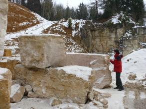 In der Bildmitte befinden sich mehrere, große Blöcke aus beigem Kalkstein. Rechts daneben steht ein Mensch mit roter Jacke. Im Hintergrund ist Wald zu sehen. Es liegt ein bisschen Schnee.