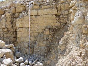 Das Bild zeigt einen Aufschluss aus gebankten, hellbeigen bis gelblichen Kalksteinen. Die Wand ist von Geröllen umgeben. Vor dem Aufschluss befindet sich ein Maßstab.
