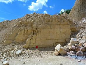 Blick auf eine Steinbruchwand aus dickbankigen (bis 1 Meter) hellen Kalksteinen. Rechts und links vor der Abbauwand liegen Gerölle. Der Himmel ist intensiv blau.