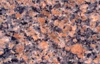 Detailaufnahme einer polierten Steinplatte. Das Gestein hat große, orange-rosane Kristalle, hellgraue Kristalle, weißliche Kristalle und schwarze, kleine Kristalle. Der Bildausschnitt hat eine Breite von 12 cm.