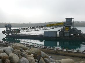 Das Foto zeigt den Transport von Abbaueimern über ein Förderband auf einem schwimmenden Bagger in einem Baggersee. Im Vordergrund sind größere Steine gelagert.