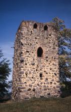 Das Bild zeigt die Front eines viereckigen Turms, welcher auf einer kleinen Erhöhung steht. Der Turm ist aus rötlich bis gelblich grauen Gesteinen gebaut und hat ein großes Fenster und oben noch kleinere Fenster.
