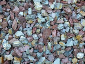 Nahaufnahme von ausgebreiteten kleinen Steinen. Die kantigen Stücke sind unterschiedlich gefärbt, von hellgrau bis zu rötlichem Braun.