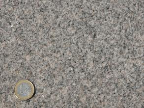 Granit aus dem Steinbruch Seebach (grauer, lokal leicht rötlichgrauer, klein- bis mittelkörniger Granit mit nur schwacher Mineralregelung).