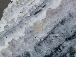 Vergrößerte Aufnahme von milchig weißen bis violettgrauen Kristallen mit nach rechts geneigter Schichtung. Rechts und unten sind auch dunklere Einschlüsse sichtbar.