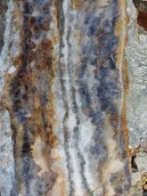 Vergrößerte Aufnahme einer kristallinen Gesteinsoberfläche mit vertikal ausgerichteten, unterschiedlichen Farbbereichen (von Brauntönen links über Weiß und Grau bis zu Blautönen rechts).