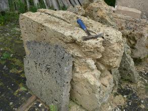 Das Bild zeigt mehrere Gesteinsplatten, seitlich, unten und oben gesägt, vorne unregelmäßig gebrochen. Die Platten sind teils grau, teils rötlich bis gelblich und verschieden dick. Ein Hammer liegt obenauf.