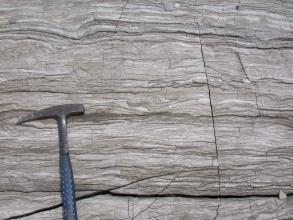 Nahaufnahme von hellgrauem Gestein mit waagrechten, dunkleren Streifen; zum Teil auch wellenförmig. Rechts verläuft ein senkrechter Riß, unten ein zuerst schräger, dann waagrechter Riß. Links zeigt ein Hammer die Größenverhältnisse an.
