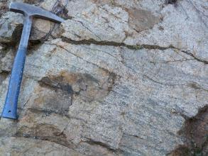 Nahaufnahme eines grauen Gesteins, welches eine deutliche Einregelung der Minerale in Bänder, welche von links oben nach rechts unten verlaufen, zeigt. Am oberen linken Bildrand befindet sich ein Hammer als Maßstab.