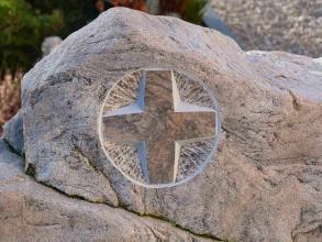 Nahaufnahme eines Grabdenkmals. In das hellbeige Gestein ist in der Bildmitte ein Kreuz in einem Kreis eingearbeitet.
