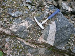 Nahaufnahme eines Aufschlusses: Das anstehende Gestein ist dunkelgrau und von hellgrauen Bändern durchzogen. Zwischen den einzlenen Blöcken befindet sich Erde mit kleinen Gesteinsbruchstücken. Auf dem Aufschluss liegt ein Hammer.