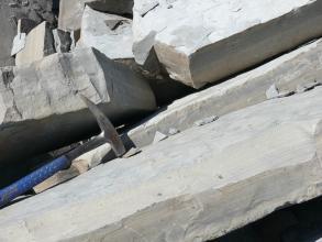 Das Bild zeigt mehrere, hinter- und übereinanderliegende, schräggestellte hellgraue Kalksteinplatten. Links liegt ein Hammer auf den Platten als Maßstab.