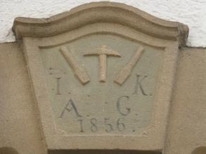 Kunstvoll gefertigtes Türschild mit Werkzeugen, Buchstaben und Jahreszahl darauf. Das Schild ist aus homogenem, beigen Kalkstein gefertigt.