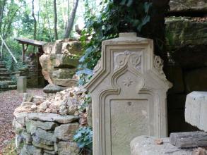 Im Vordergrund des Bildes ist eine kunstvolle Bildhauerarbeit aus hellbeigem Kalksandstein zu sehen. Im Hintergrund sind Mauern aus dem gleichen Gestein, ein belaubter Platz und Wald zu erkennen.