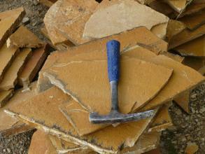 Auf diesem Foto liegen mehrere orangefarbene, in unterschiedlichen Größen und Formen gebrochene, dünne Gesteinsplatten auf- und nebeneinander. Ein Hammer auf der obersten Platte dient als Größenvergleich.