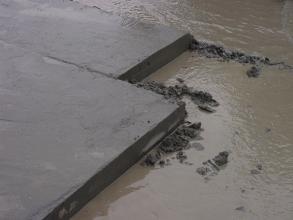 Blick von schräg oben auf eine dunkelgraue Gesteinsplatte, welche sich auf der linken Bildhälfte befindet. Rechts neben einer scharfen Bruchkante liegt etwas Geröll und eine Oberfläche aus matschigem Wasser ist zu erkennen.