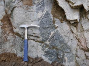 Nahaufnahme eines hellgrauen Gesteins, in welches in der Bildmitte dunkleres Gestein eingeschlossen ist. Der dunkelgraue Einschluss ist länglich und unförmig. In den Klüften des Gesteins befindet sich braune Erde. Links liegt ein Hammer.