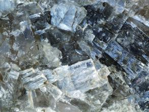 Nahaufnahme von splittrigem, milchigem bis durchsichtigem Gestein unterschiedlicher Größe und Farbe.