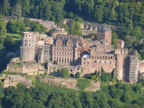 Blick von erhöhtem Standort auf die rötlichen Mauern von Schloss Heidelberg. Die Türme links und rechts außen sowie ein Anbau sind für Sanierungsarbeiten eingerüstet.