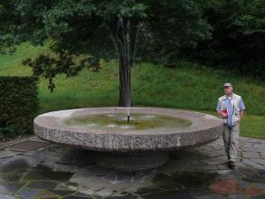 Das Bild zeigt einen schüsselförmigen Brunnen aus rosa Gestein. Der Brunnen ist wassergefüllt und in der Mitte befindet sich eine kleine Fontäne. Der Brunnen steht auf einer mit ebenfalls rosa Platten gepflasterten Fläche, im Hintergrund ist Wiese.