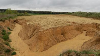 Das Bild zeigt die oberste Schicht einer Sandgrube. Die nach unten abfallenden Wände links und rechts sind rötlich braun und zerfurcht. Darunter breitet sich gelber Sandboden aus. Die seitlichen Ränder der Grube bilden bewachsene, längliche Hügel.