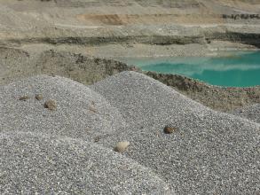 Im Vordergrund sind mehrere graue Kieshalden zu sehen. Dahinter erblickt man einen See sowie die hellbraunen Abbauwände einer Kiesgrube.