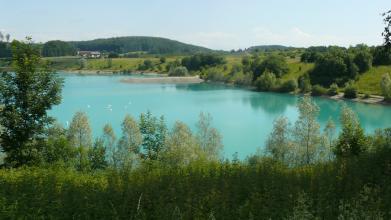 Blick über Baumwipfel auf einen hellblauen See und die angrenzende, von Bäumen bestandene Uferböschung. Im Hintergrund ragt ein aufgeschütteter Dammweg in den See. Auf dem See schwimmen Schwäne.