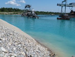 Das Bild zeigt den Abbau von Kies aus einem See mittels Schwimmbagger. Links vorne schiebt sich ein Kieshang in den See.