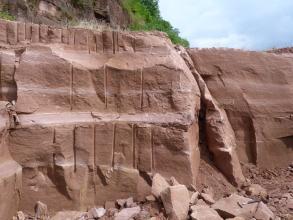 Das Bild zeigt zwei versetzt stehende Steinbruchwände. Auf dem rötlich braunen Gestein sind links mehrere senkrecht verlaufende Furchen zu erkennen. Unten rechts liegt ein Hammer auf einem losen Block.