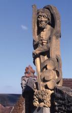 Die Aufnahme zeigt eine an einer erhöht stehenden Mauer angebrachte, aus gelblich grauem Gestein gefertigte Figur eines bärtigen Mannes.