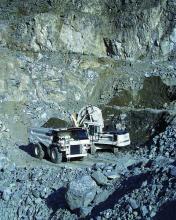 Das Bild zeigt einen Steinbruch mit mehreren Abbausohlen, in welchem graues Gestein ansteht. In der Bildmitte, auf der untersten Sohle, befinden sich zwei Fahrzeuge zur Gewinnung und Steinverladung.