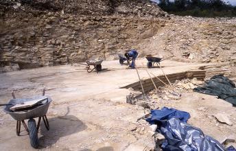 Blick in einen Steinbruch mit halbhoher Wand im Hintergrund und ebener Sohle vorne. Rechts ist ein Stück der Sohle abgebrochen. Ein Arbeiter befindet sich auf der Sohle, zusammen mit vier befüllten Schubkarren.