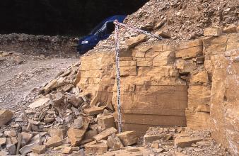 Blick auf einen nach links abfallenden Steinbruchhügel mit Festgestein und davorliegendem Schutt. In der Bildmitte zeigt eine Messlatte die Höhe der festen Steinblöcke.