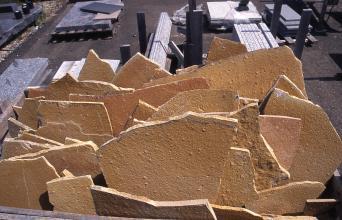 Blick auf hinter- und nebeneinander gestapelte, dünne Bruchstücke von rostbraunem Gestein.