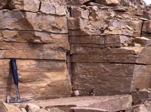 Teilansicht einer Steinbruchwand; zu sehen ist waagrecht gebanktes, plattiges Gestein in rostbrauner Farbe. Ein angelehnter Hammer links dient als Größenvergleich.