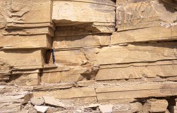 Teilansicht einer Steinbruchwand; das gelbliche, plattige Gestein ist waagrecht gebankt. Ein zwischen den Lagen aufgestellter Kugelschreiber dient als Größenvergleich.