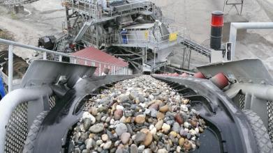 Blick von oben auf ein Förderband und eine Fördermaschine. Auf dem Förderband liegen zahlreiche kleine und größere Steine.