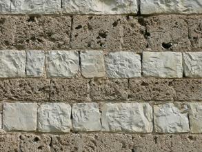 Nahaufnahme einer Steinmauer, wechsellagig gesetzt aus zwei unterschiedlichen Materialien: weißliche schraffierte Blöcke, quadratisch bis rechteckig, sowie größere und kleinere graue Blöcke mit löchriger Oberfläche.