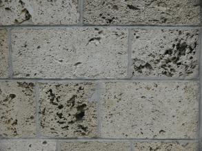 Nahaufnahme einer Gebäudefassade aus hellgrauen Steinquadern, teils mit feinen Löchern, teils mit größeren Poren.