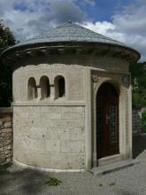 Blick auf eine kleine, runde Kapelle. Die Kapelle ist aus hellgrauem Gestein erbaut und weist rechts eine Holztür, links kleine Bogenfenster sowie Verzierungen auf. Das runde, schirmartige Dach besteht aus bläulichen Ziegeln.