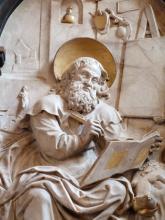 Nahaufnahme einer Heiligenfigur aus beige-grauem Stein mit gelblichen, vielleicht vergoldeten Stellen. Die Figur hält Schreibgerät und ein Buch in den Händen. Rechts unten ist ein Stierkopf zu erkennen.