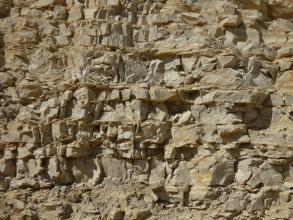 Seitlicher Blick auf eine aus teils würfelförmigen, teils rechteckigen hellbraunen Blöcken zusammengesetzte Gesteinswand.