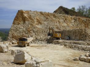 Das Bild zeigt Bagger und Ladefahrzeug vor einer bräunlich grauen, links schräg abgechnittenen Steinbruchwand. Oben rechts befindet sich wie ein Aufbau eine bewaldete Böschung. Vorne links liegen größere, würfelförmige Quader.
