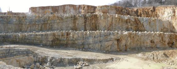 Panoramabild eines in Betrieb befindlichen Steinbruches mit drei Sohlen. Das Gestein wechselt von bräunlich bis zu blaugrau. Im Vordergrund links sieht man eine Auffahrtsrampe. Rechts oben ist eine bewaldete Böschung.