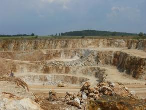 Blick auf einen Steinbruch aus hellem, orange anwitterndem Kalkstein. Der Abbau wird in mehreren Sohlen betrieben. Im Hintergrund ist ein kleiner, bewaldeter Hügel zu erkennen.