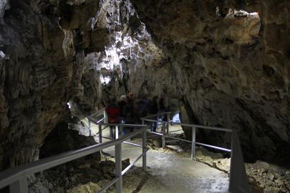 Blick in das Innere einer Höhle. Ein schwach beleuchteter Laufgang mit seitlichen Brüstungen führt im Zickzack durch die Höhle. Eine Wand oberhalb der Bildmitte ist ebenfalls schwach erhellt.