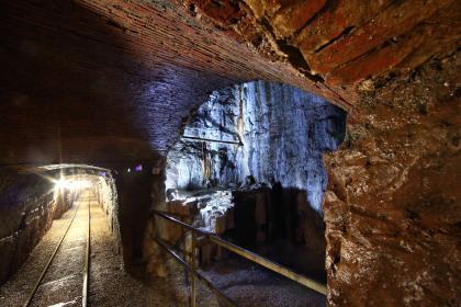 Blick in das Innere eines Besucherbergwerks. Rechts öffnet sich im Gestein ein höhlenartiger Raum, der bläulich angestrahlt und mit einem Gitter gesichert ist. Links unten führen Gleise in einen langen, ausgeleuchteten Schacht.